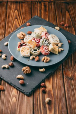 Traditional oriental sweets and nuts: hazelnuts, cashews on a brown wooden background. Turkish dessert is the locus of Rahat. View from above. Place under the text