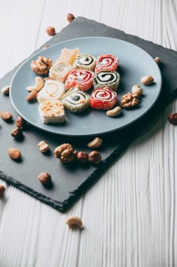 Traditional oriental sweets and nuts: hazelnuts, cashews on a white wooden background. Turkish dessert is the locus of Rahat. View from above. Place under the text