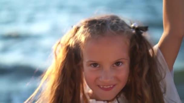 Gyerek lány játszik vele lófarok szőr a tenger közelében