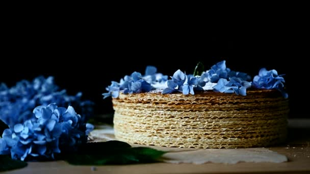 white powdered sugar is sprinkled on a waffle cake decorated with blue flowers