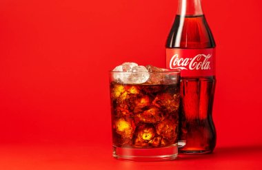 MINSK, BELARUS - APRIL 14, 2018: Classic bottle of Coca-Cola and glass with ice and beverage on red background. Coca Cola drinks are produced and manufactured by The Coca-Cola Company.