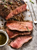 Photo Sliced Roast beef on white paper on wooden table with grilled vegetables