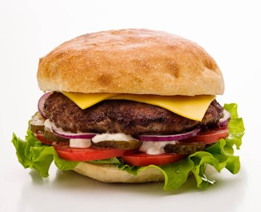 Classic cheeseburger with salad, tomato and pickled cucumbers on a white background. Isolated.