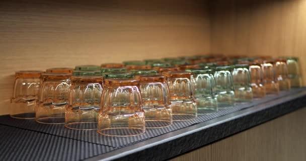 Zaměřit přechod sklenic na vodu nebo džus. Sklenice na pití různých barev v dřevěné kuchyňské skříni.