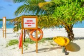 Fotografie Emergency Equipment on a Beach with a Palm Tree in Maledives