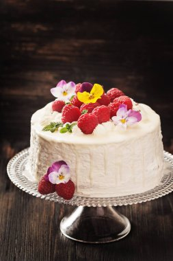Festive cake with raspberries and flowers with streaks of glaze on  black background