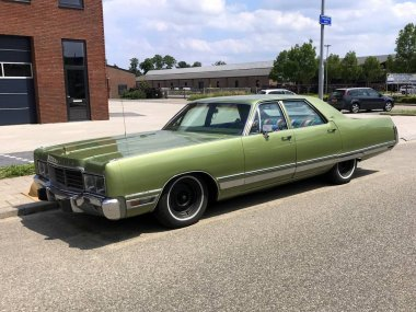 Woerden, the Netherlands - June 22, 2019: Green Chrysler New Yorker parked by the side of the road. Nobody in the vehicle.