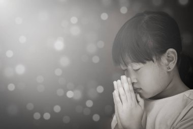 Asian face Child praying and worship to GOD Using hands to pray in religious beliefs and worship christian in the church or in general locations in  White and Black background