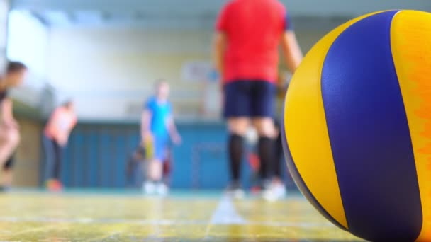 Trenér trénuje volejbal ve škole.
