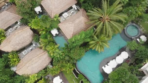 Aerial Drone Flight top down Blick auf Luxushotel mit Strohdachvillen und Pools im tropischen Dschungel und Palmen. Luxuriöse Villa, Pavillon im Wald, Ubud, Bali