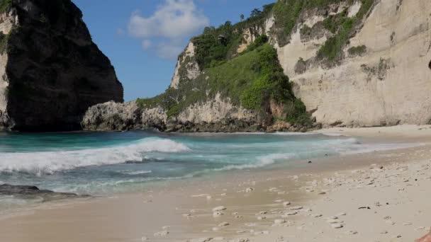 Hübsche Frau zu Fuß zum Meer mit Felsen und türkisfarbenem Meer, blauem Himmel. Atuh Strand, Insel Nusa Penida, Bali, Indonesien. Tropischer Hintergrund und Reisekonzept.