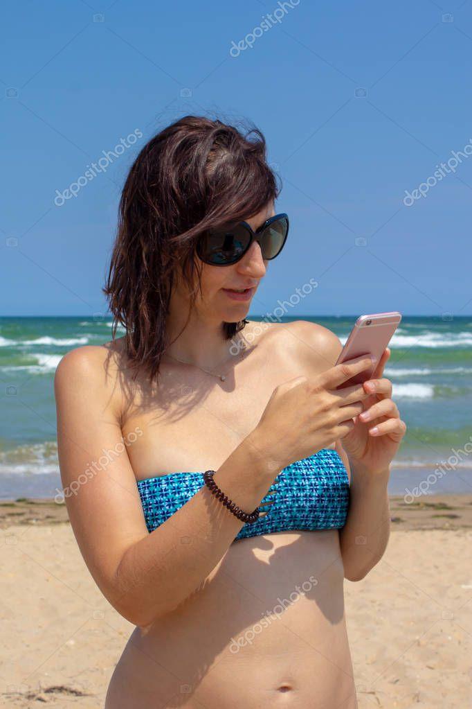 Attractive caucasian beautiful woman in bikini texting on the background of the sea  on beach