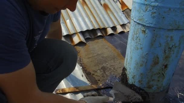 Oprava střechy v prostoru komínu pomocí hořáku.