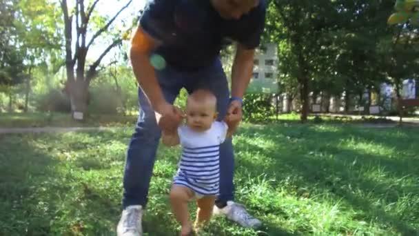 Kleines Baby lernt laufen. Erste Schritte. Eltern bringen ihrem Kind bei, die ersten Schritte im Sommer auf einer grünen Wiese zu machen. Glückliche Kindheit und Elternschaft Konzept. Familienliebe