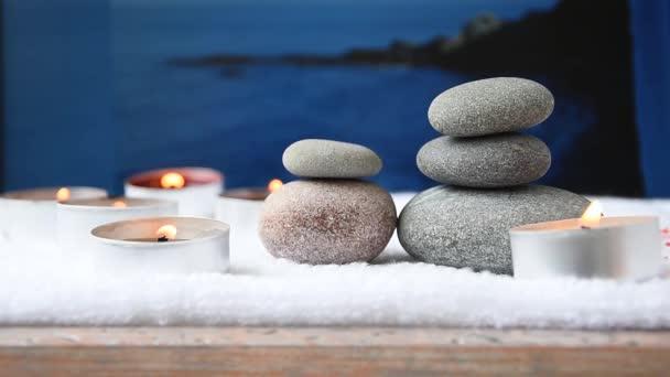Zen kameny oblázky a hořící vonné svíčky na pozadí okna, lázeňský koncept pro léčení meditace, masáže relaxační