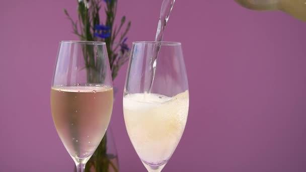Šampaňské. Dvě flétny se šumivým vínem na purpurovém pozadí. Nalít šampaňské.