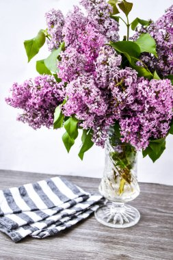 Lilac spring bouquet in glass vase on table with scissors and rope, copy space, holiday congratulation background