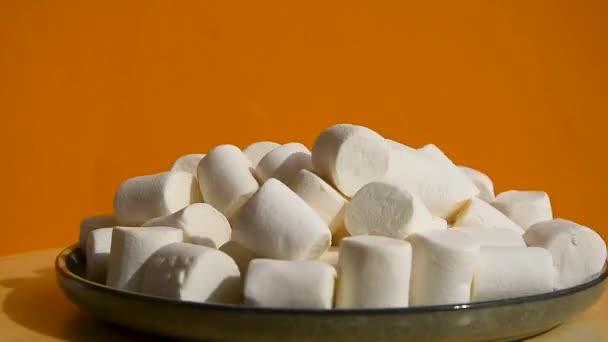 Bílé marshmallows na desce rotující na žlutém pozadí. Pozadí jídla. Nezdravé sladké jídlo.