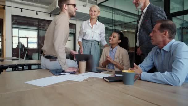Skupina spokojených multiraciálních podnikatelů diskutuje o projektu nebo nové obchodní strategii při setkání v moderním kancelářském nebo spolupracujícím prostoru, těší se z společné práce