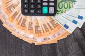 Kalkulačka a europeníze na šedém dřevěném stole. Eurobankovky s černou kalkulačkou na dřevěném pozadí. Kopírovat prostor pro text. Financování a koncepce rozpočtu.