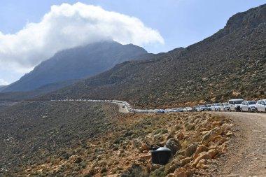 Greece, a line of traffic on gravel road to Balos Lagoon on Gramvousa peninsula