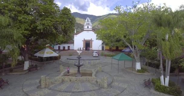Olaja, Antiokvia / Kolumbie - 25. ledna 2020: Fontána uprostřed náměstí, Minivan zaparkované v ulici a Village Church s několika domy kolem něj a mnoho stromů