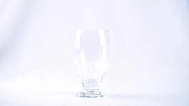Eiswürfel werden in einen gläsernen Becher auf weißem Hintergrund geworfen
