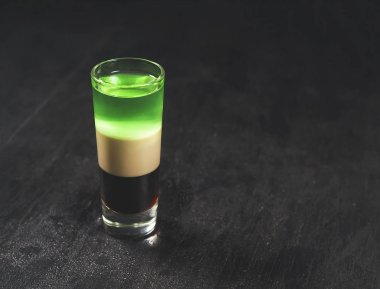 Variety of colorful green blue yellow red and white beautiful alcohol sweet shooters shots cocktail fresh beverage in small glasses standing in row on bar studio closeup, horizontal picture stock vector