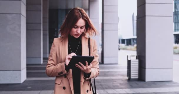 Üzleti nő használja a digitális Tablet Walking a városban. Lassú mozgás Gimbal stabilizálódott. Női vállalkozó hálózatépítés az interneten, gépelés, sms-ezés, tanulás online, rohanás az irodába reggel.