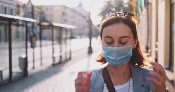 Žena vzlétá z ochranné masky, aby se nadechla ve městě. Pomalu, Gimbale Stabilizátore. Dívka v masce proti znečištění vzduchu a koronaviru Covid-19, venku a na ulici.