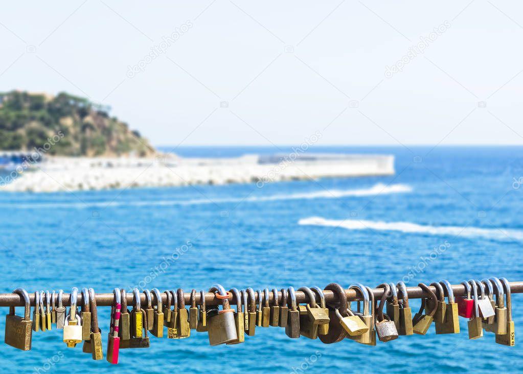 Padlocks on rope, blue sea background