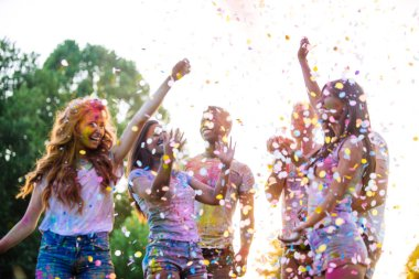 Group of teens playing with colors at the holi festival, in a park stock vector