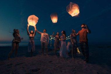 Genç millenials holding ve gökyüzü fener - Lantern Festivali sahilde tutuşabilme