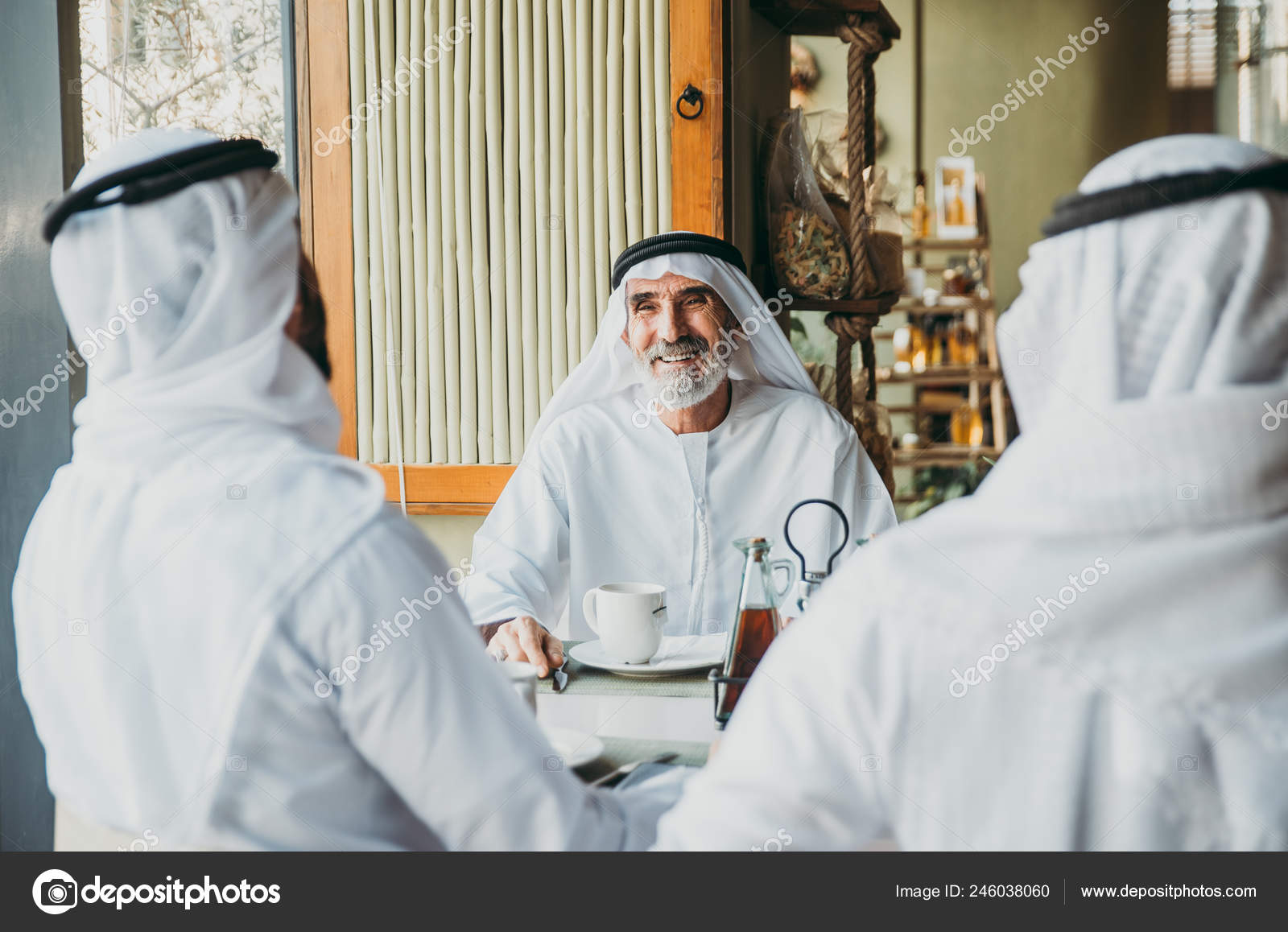 Three Business Men Having Tea Dubai Wearing Traditional Emirati