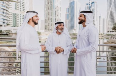 Three business men walking in Dubai wearing traditional emirati clothes