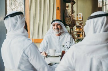 Three business men having a tea in Dubai wearing traditional emirati clothes