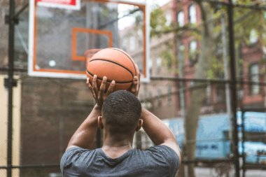 Afro-american basketball player training on a court in New York - Sportive man playing basket outdoors