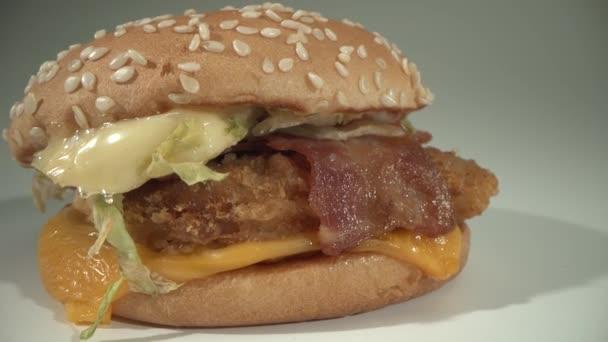 Lahodný chutný hamburger leží na bílém stole. Makro food shot ze sondy Laowa 24 mm
