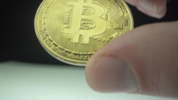 Männliche Hand hält Gold-Kryptocoin Bitcoin btc in Makroaufnahme. Weiße Oberfläche und schwarzer Hintergrund. Blockchain-Technologie.