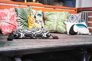 A simple couch in wood with colorful pillows and cushions, shot with analogue film photography