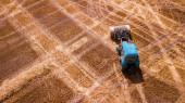 Erial nézet modern mezőgazdasági berendezések, gépek, traktor betakarítja a búzamezőt. szezonális munkák. Drónlövés. kép helyet a szöveges. Mezőgazdasági földterület felülről