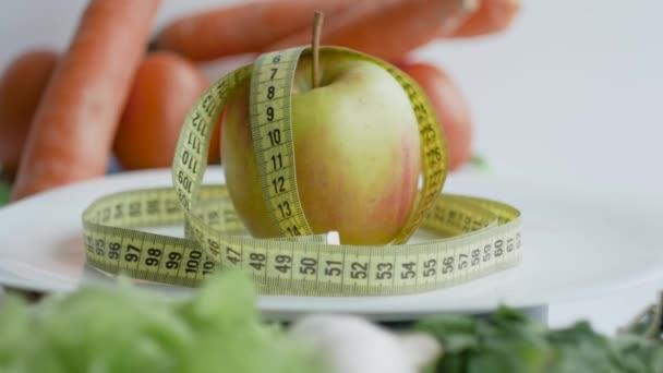Rotující jablko s měřicí páskou na talíři. Zelenina na pozadí.