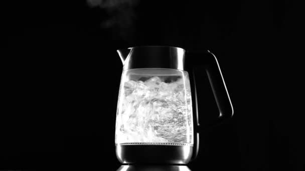 Electric kettle boil the hand takes it. Black background