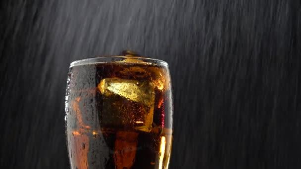 Bere in un bicchiere con ghiaccio e gocce dacqua a goccia. Priorità bassa nera