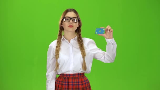 Teenage raises a card and points at it, she smiles. Green screen