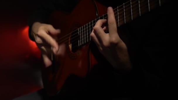 Kytaru hrají melodii člověka. Zblízka. Světlo zezadu