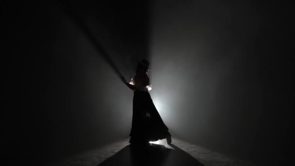 Mädchen tanzt mit Hut und einem schönen Kleid mit Kastagnetten in den Händen. Licht von hinten. Hintergrund: Rauch