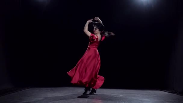 Dancer performs elegant movements with her hands in the dance. Black background