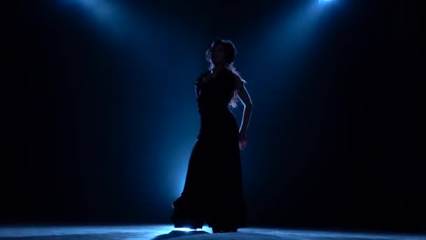 Dancer performs professional flamenco movements. Llight from behind. Smoke background. Silhouette