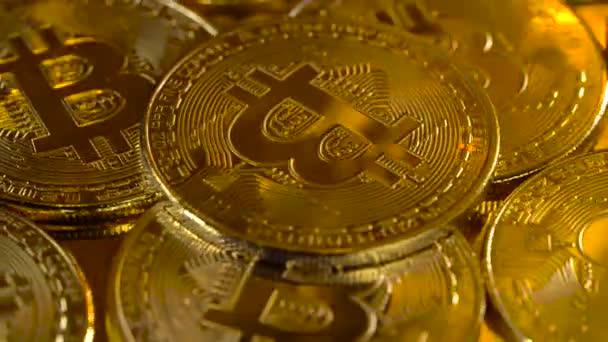 Luxusní zlaté mince jsou že kryptoměn bitcoin se pomalu otáčí v kruhu. Makro snímek rotujícího bitcoinů
